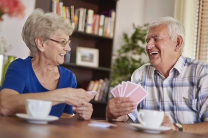 elderly couple playing cards at a table