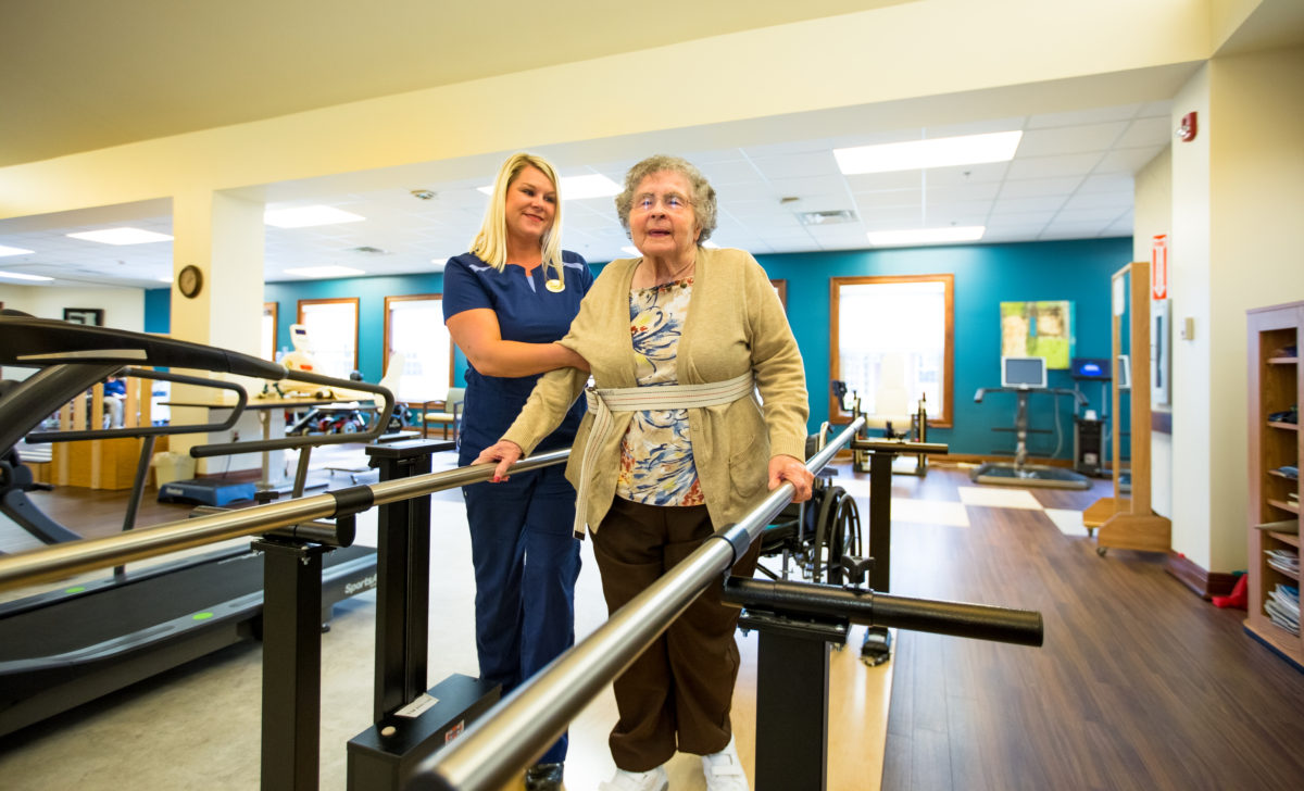 nurse assisted resident on a walker